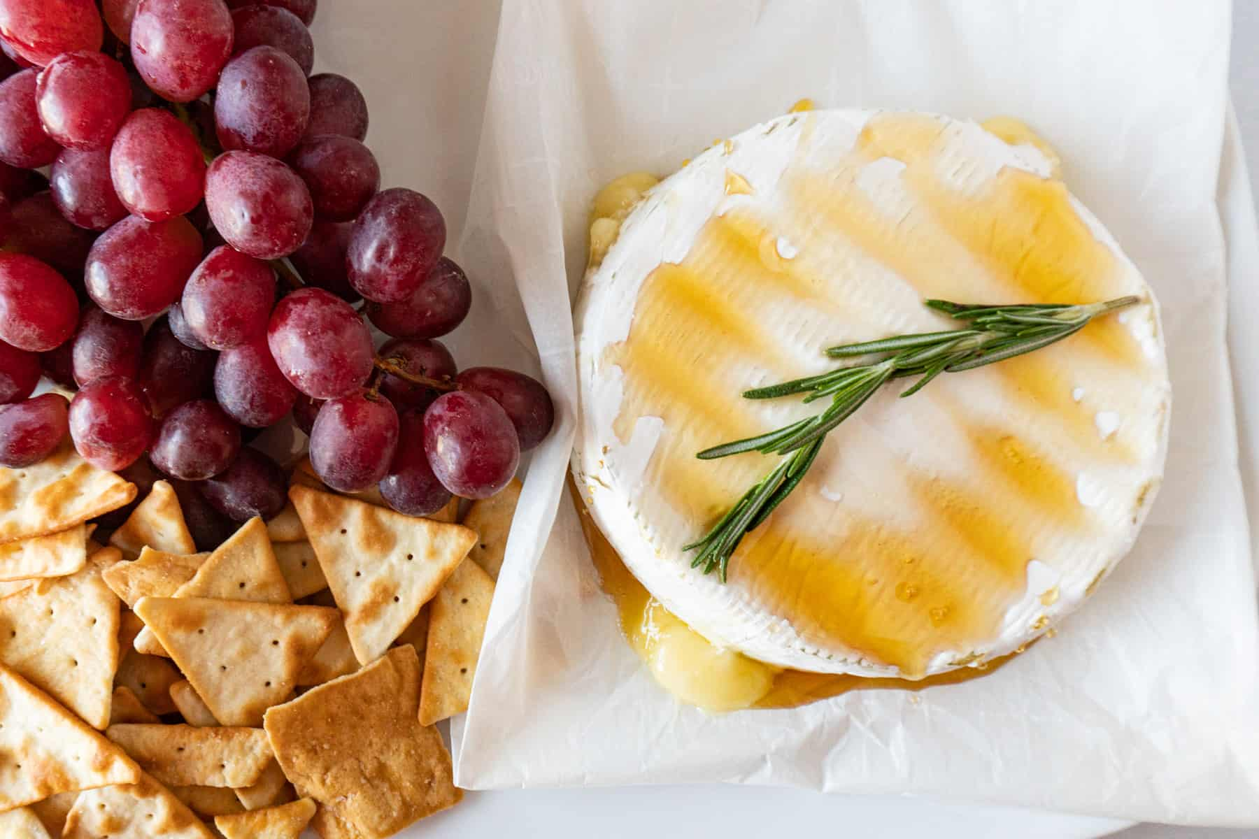 brie with honey and rosemary next to crackers and grapes