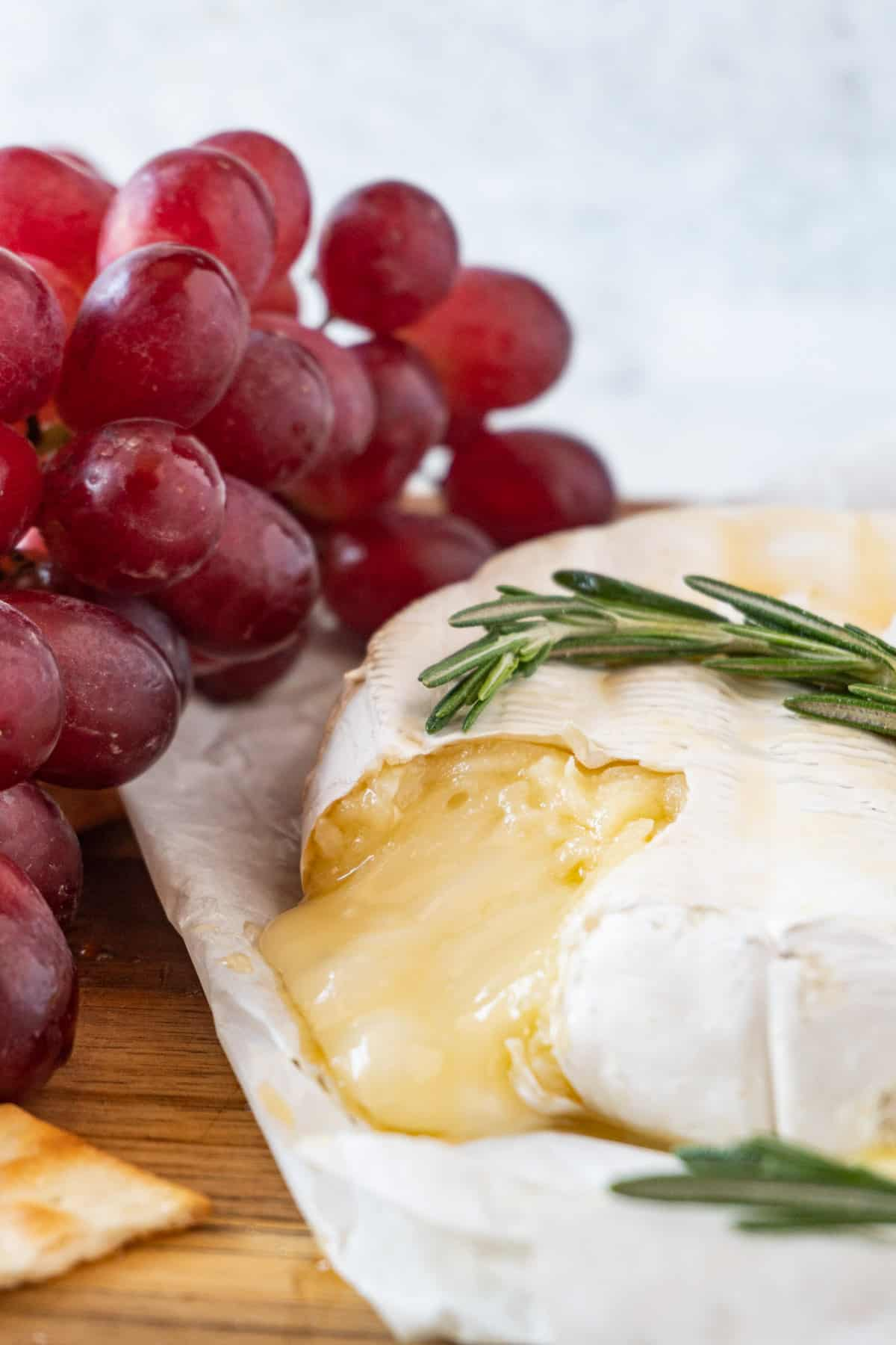 brie with melted cheese pouring out with grapes in background