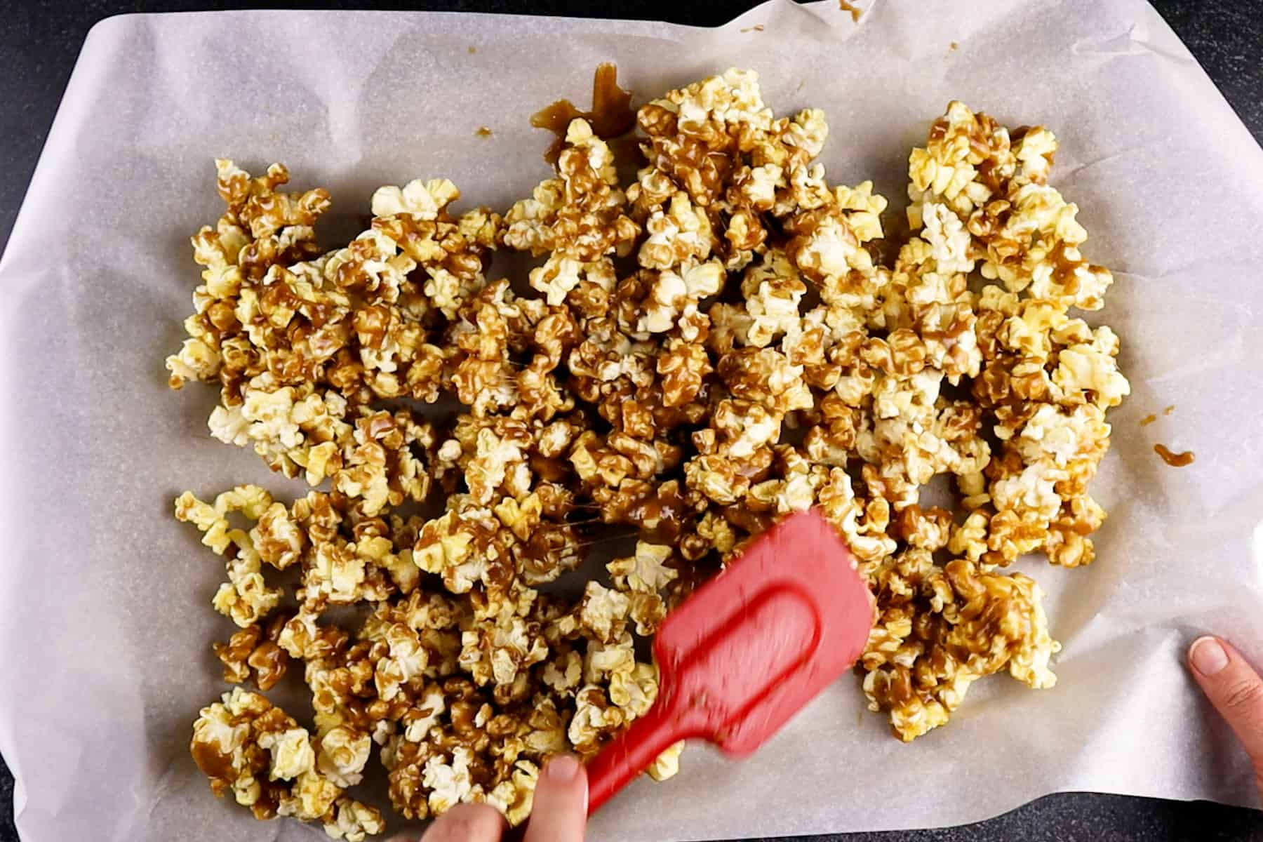 stirring popcorn on baking sheet after it has baked for 15 minutes