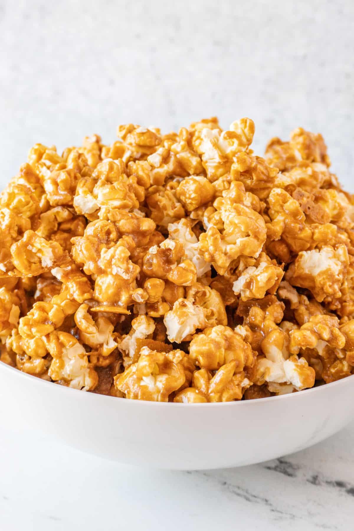 caramel popcorn piled high in large white bowl