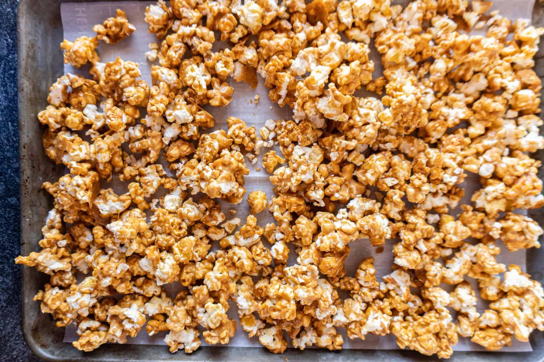 caramel popcorn after being baked on baking sheet
