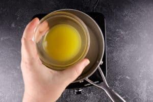 adding orange juice to sauce pan
