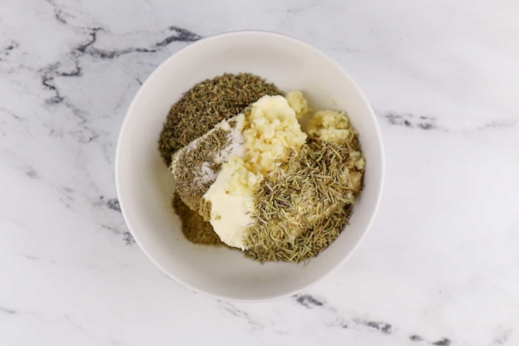 butter and herbs in bowl before mixing