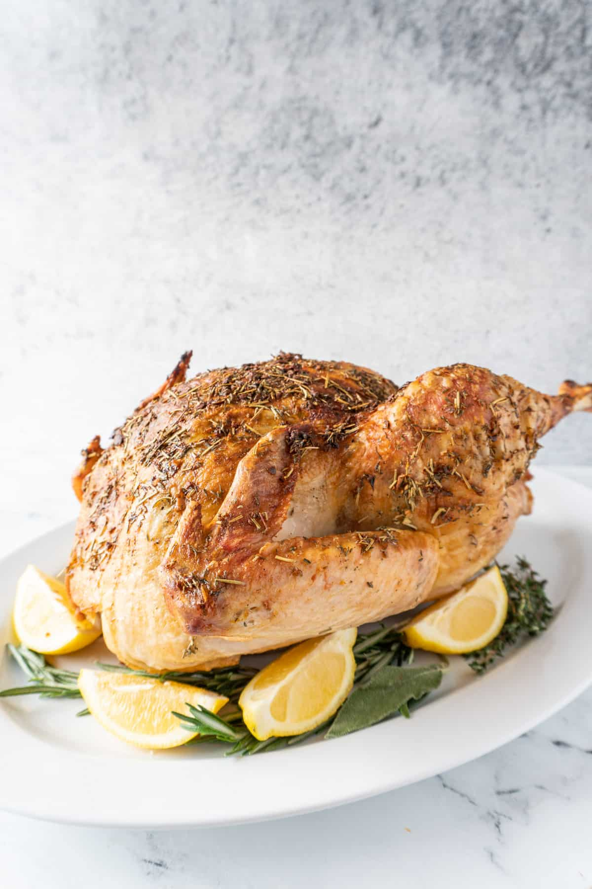 baked turkey on platter with lemon and sage leaves around it