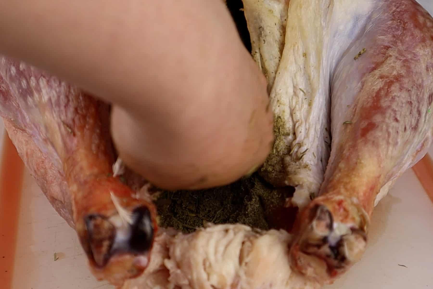 putting herb mixture in turkey cavity