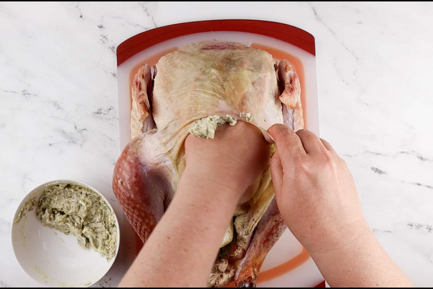 rubbing butter under the skin of turkey