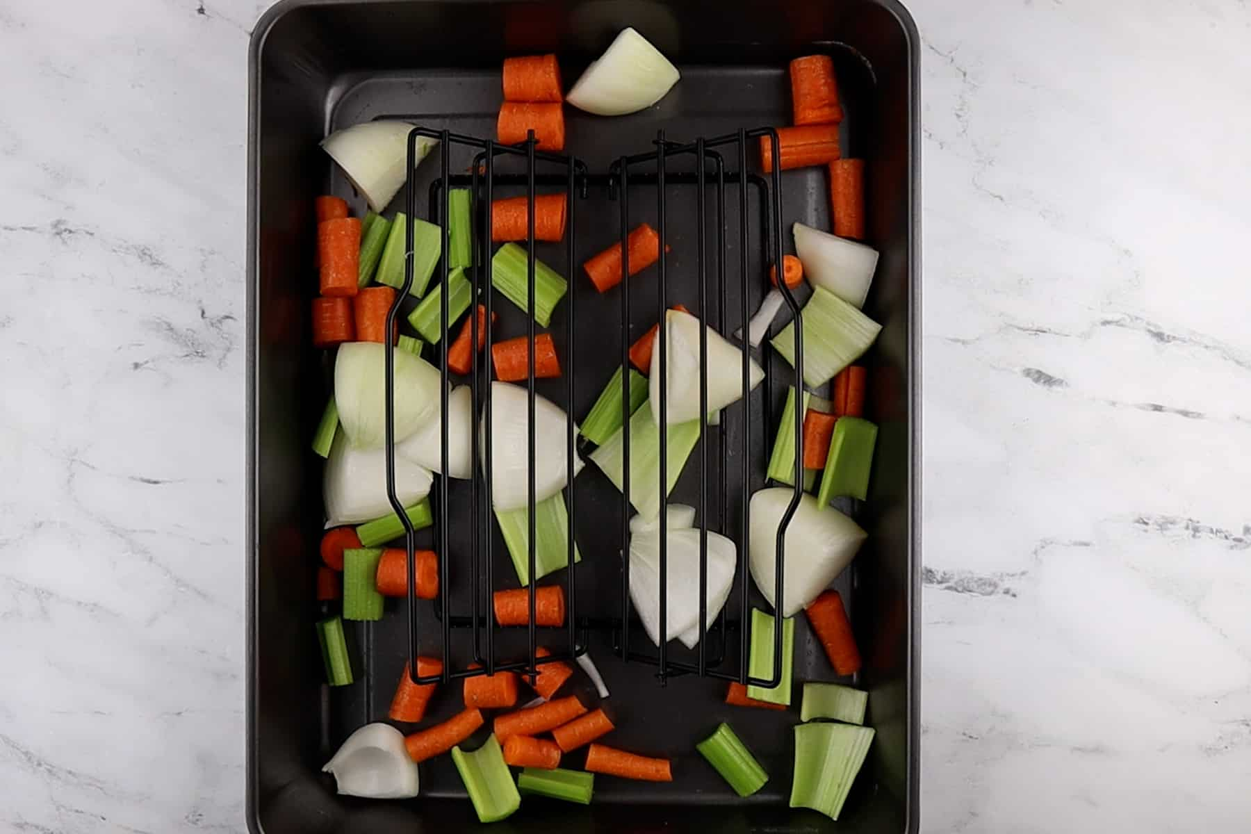 roasting pan with rack and carrots, celery, and onion