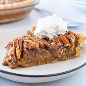 slice of pecan pie on plate with whipped cream featured image