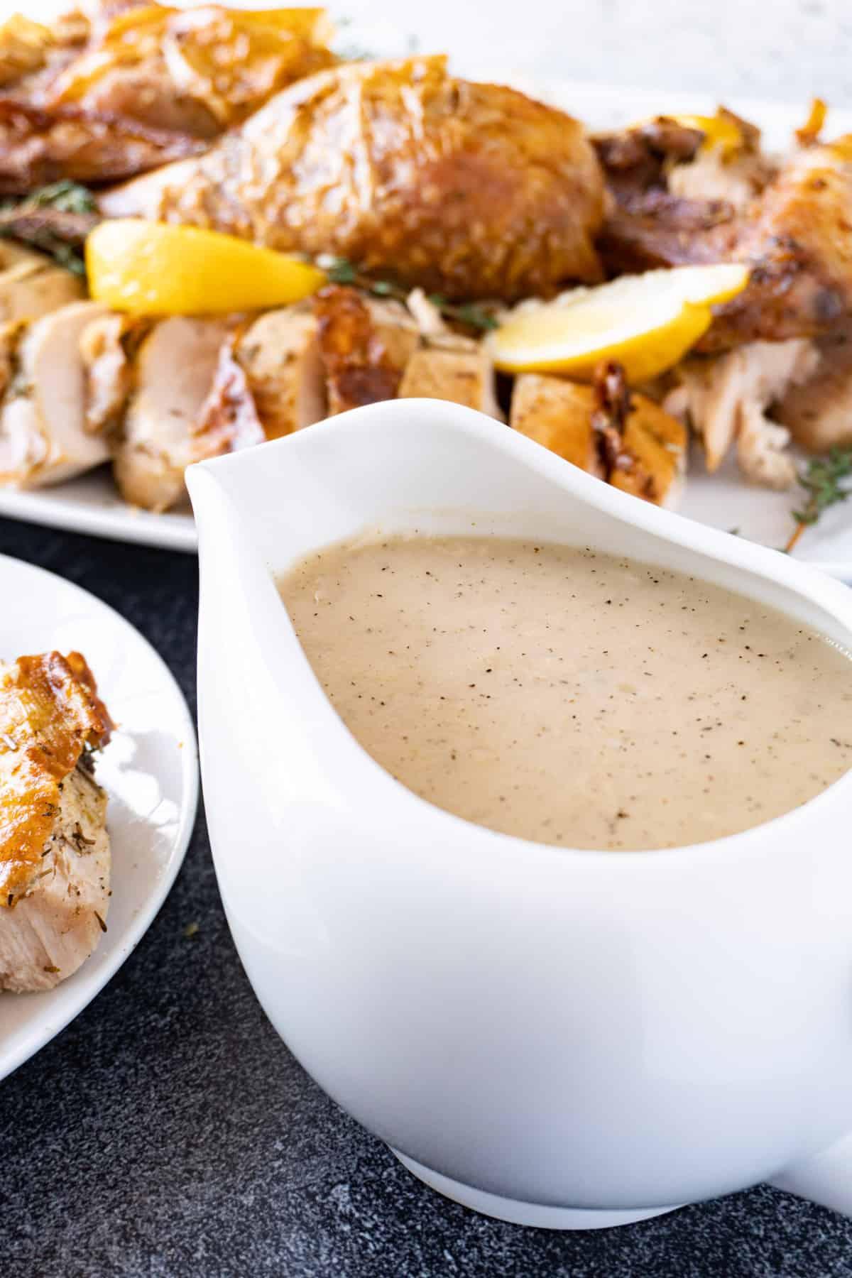 gravy in a gravy boat with turkey in background