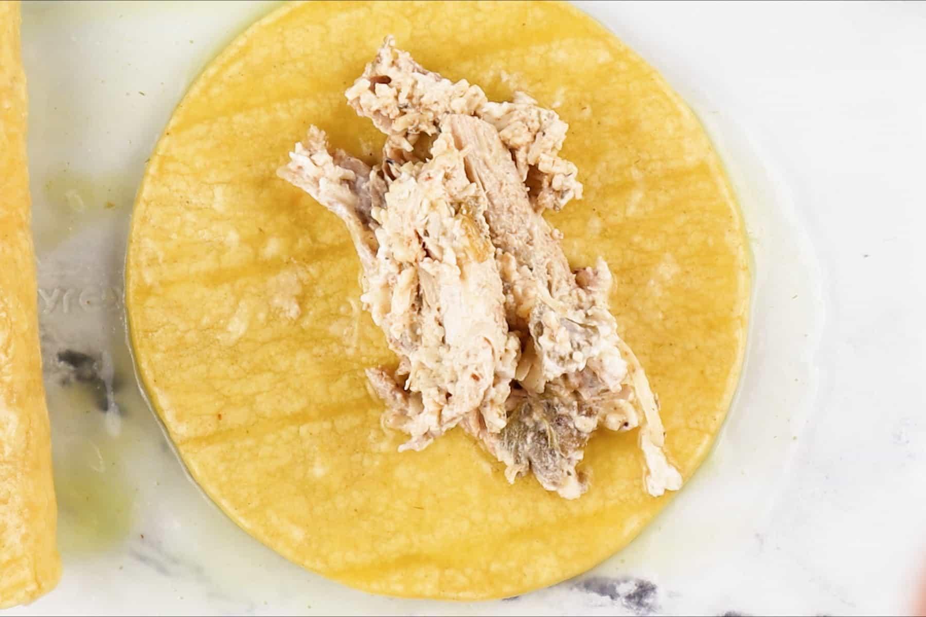 adding turkey filling to corn tortilla