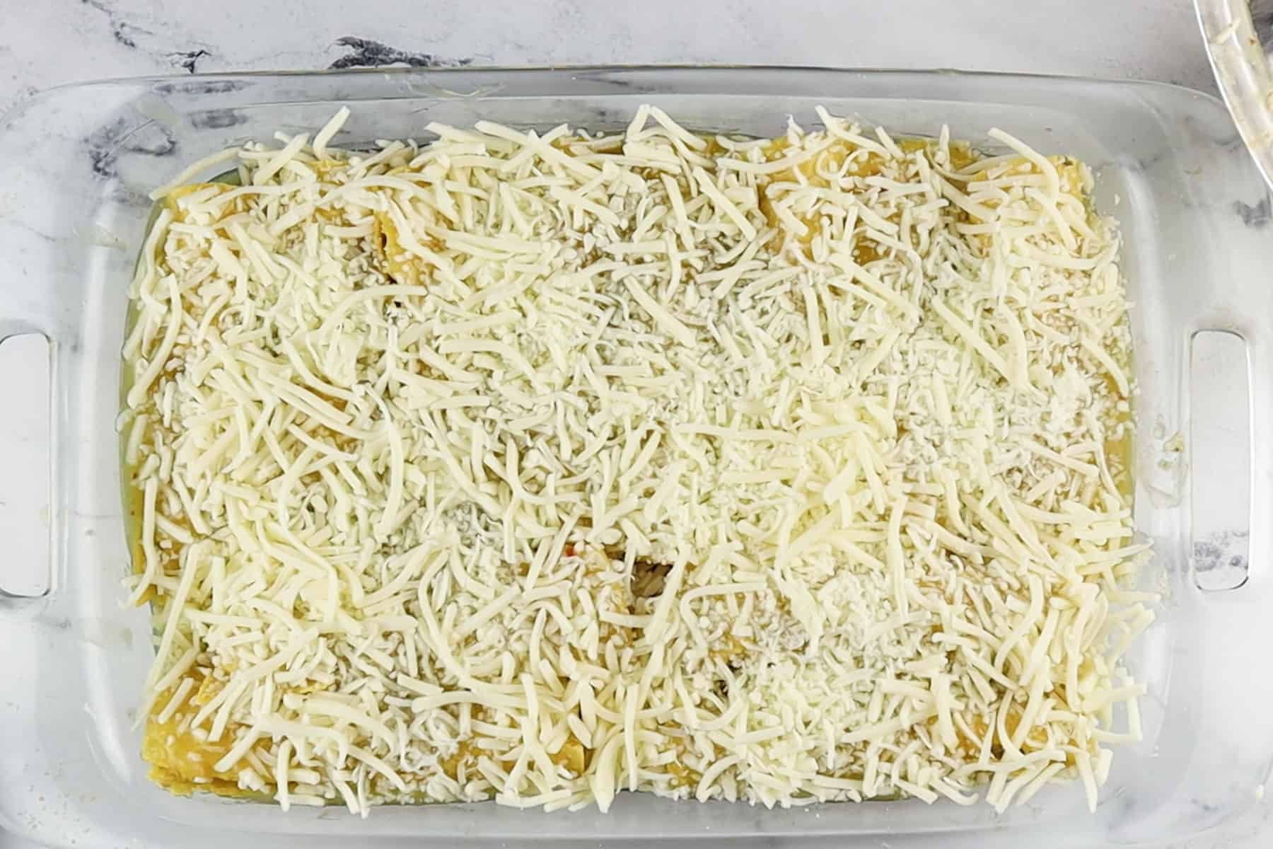 enchiladas in baking dish before baking and melting cheese