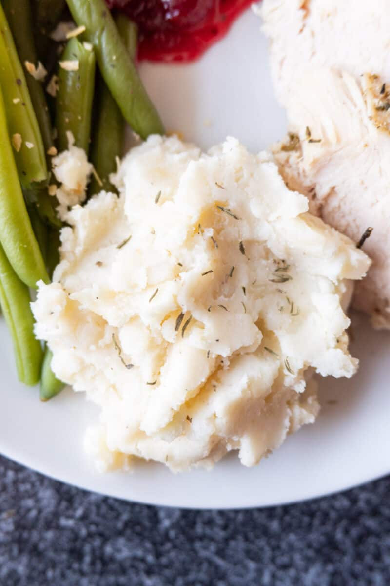 close up of mashed potatoes on plate with green beans
