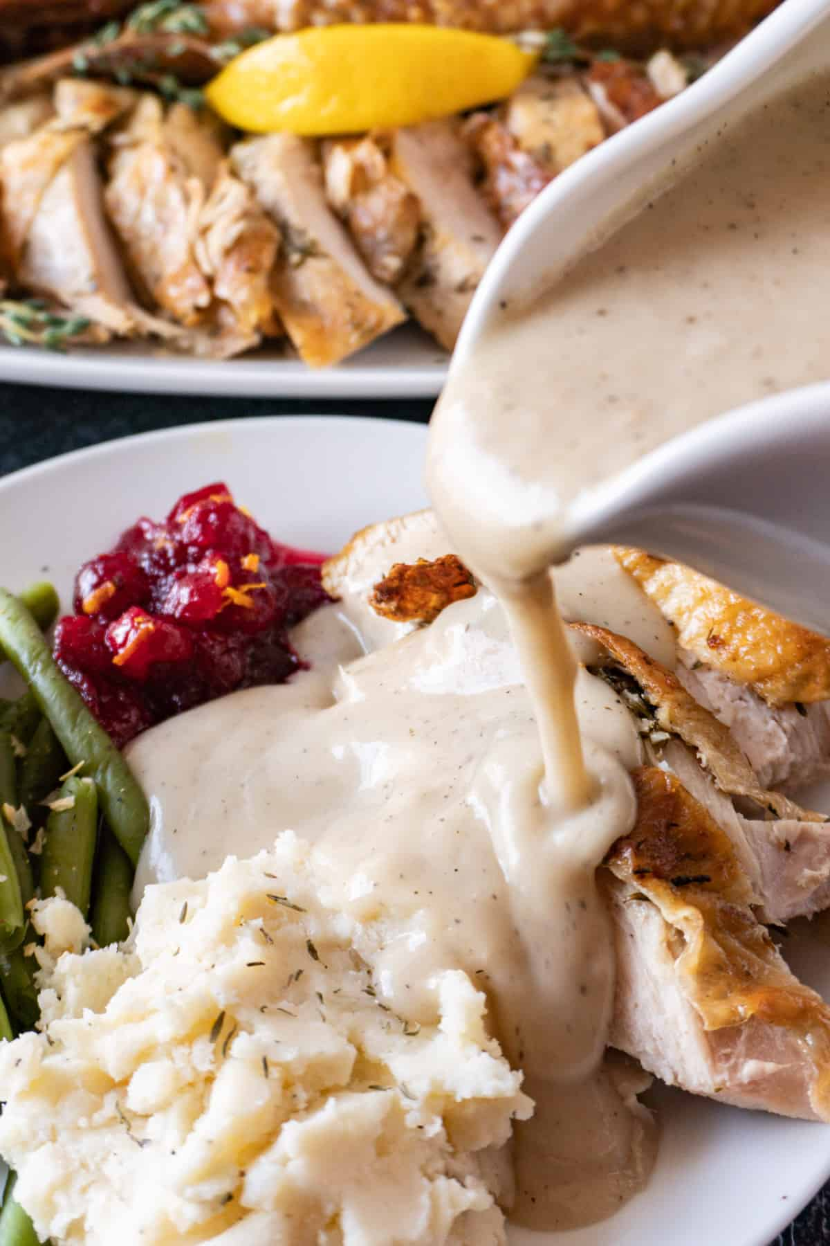 pouring gravy over plate of food including mashed potatoes