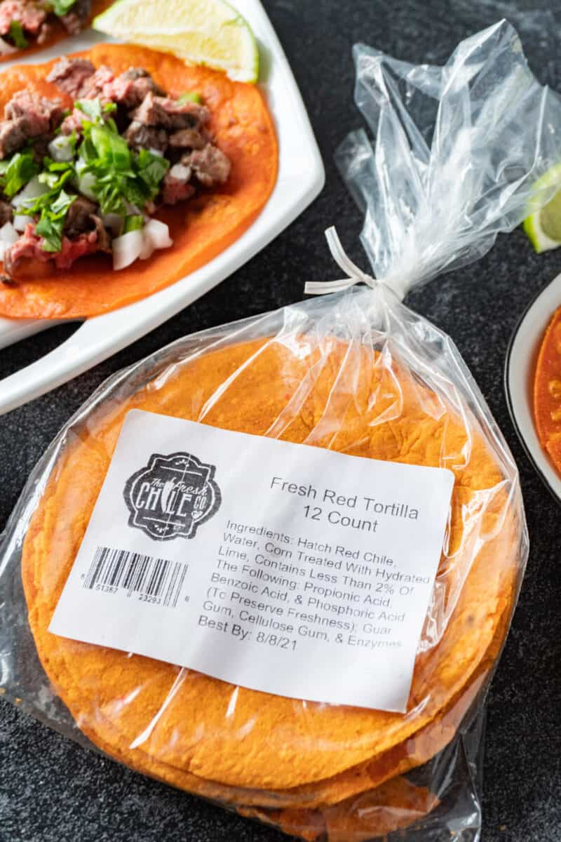 red chile corn tortillas in package with tacos in background