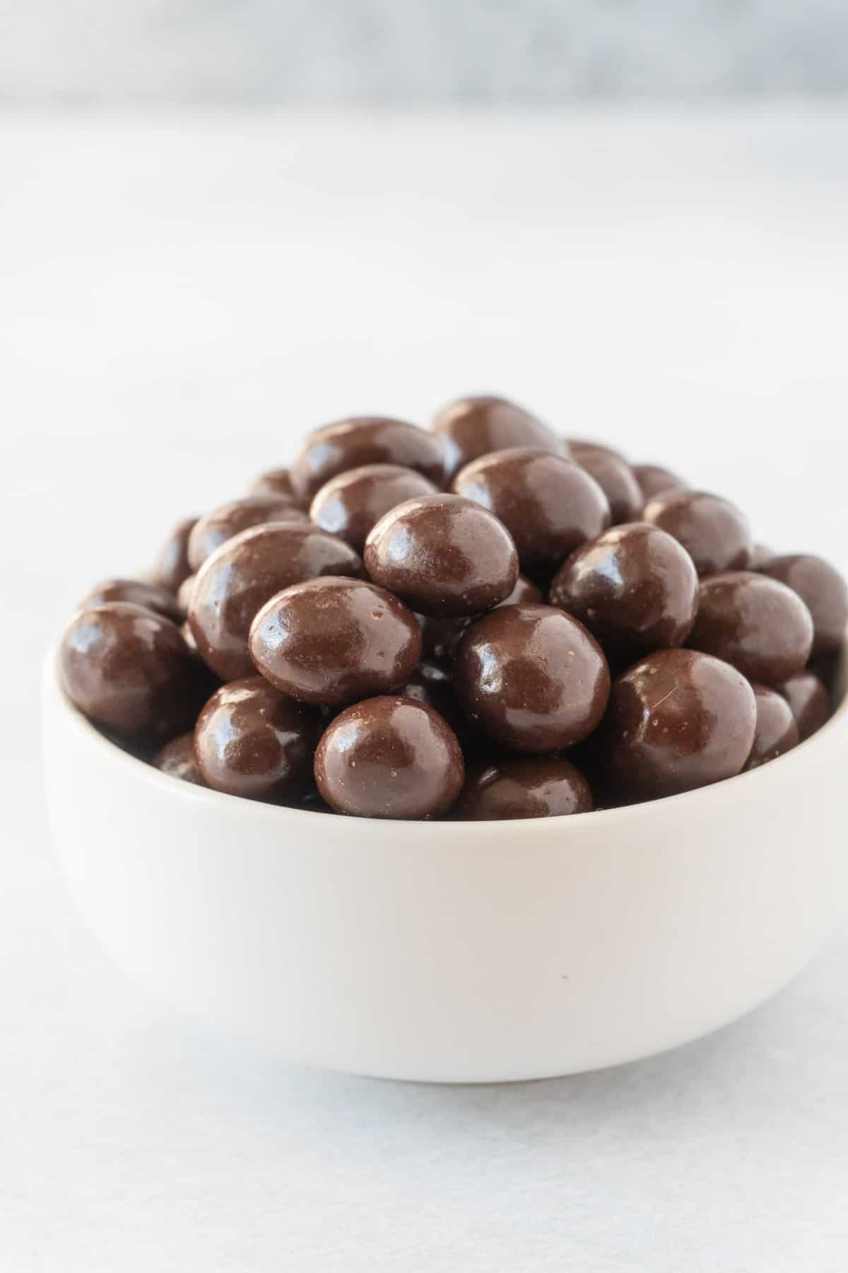 chocolate covered coffee beans in white bowl