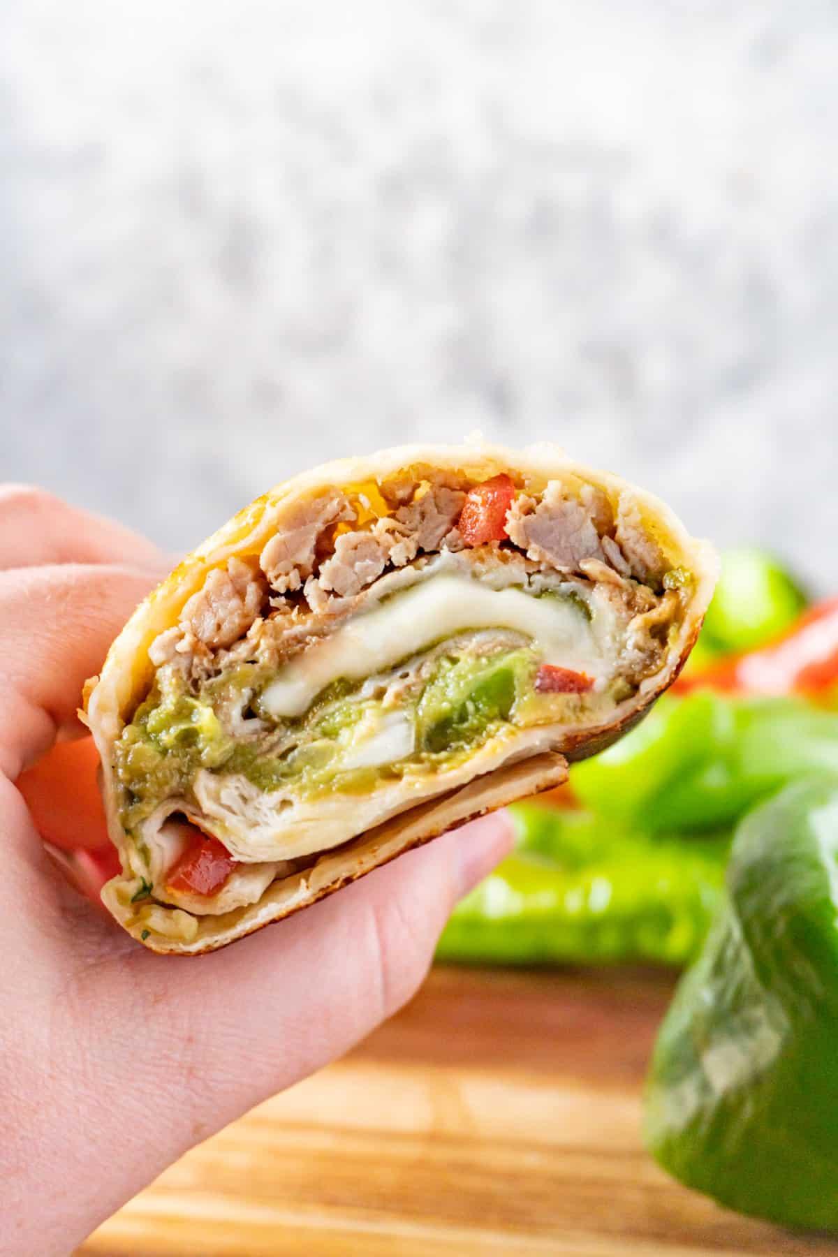chile relleno burrito cut in half held in hand