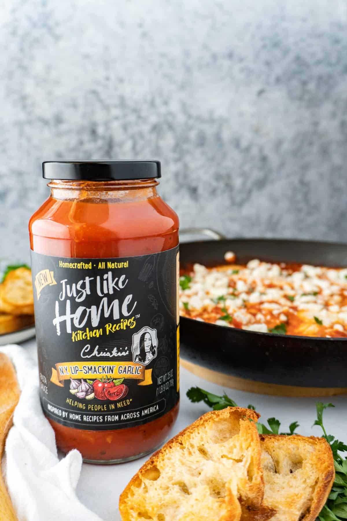 pasta sauce jar with shakshuka in background