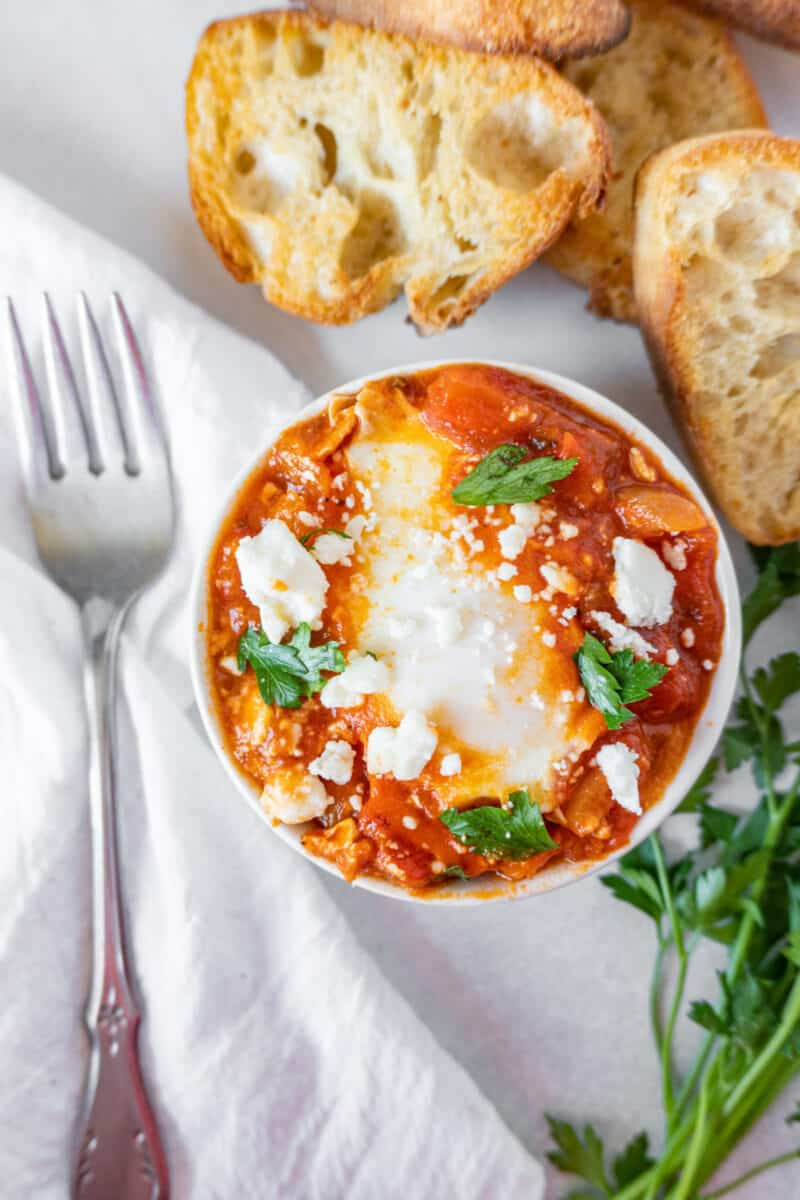 close up of shakshuka in white bowl with toasted bread