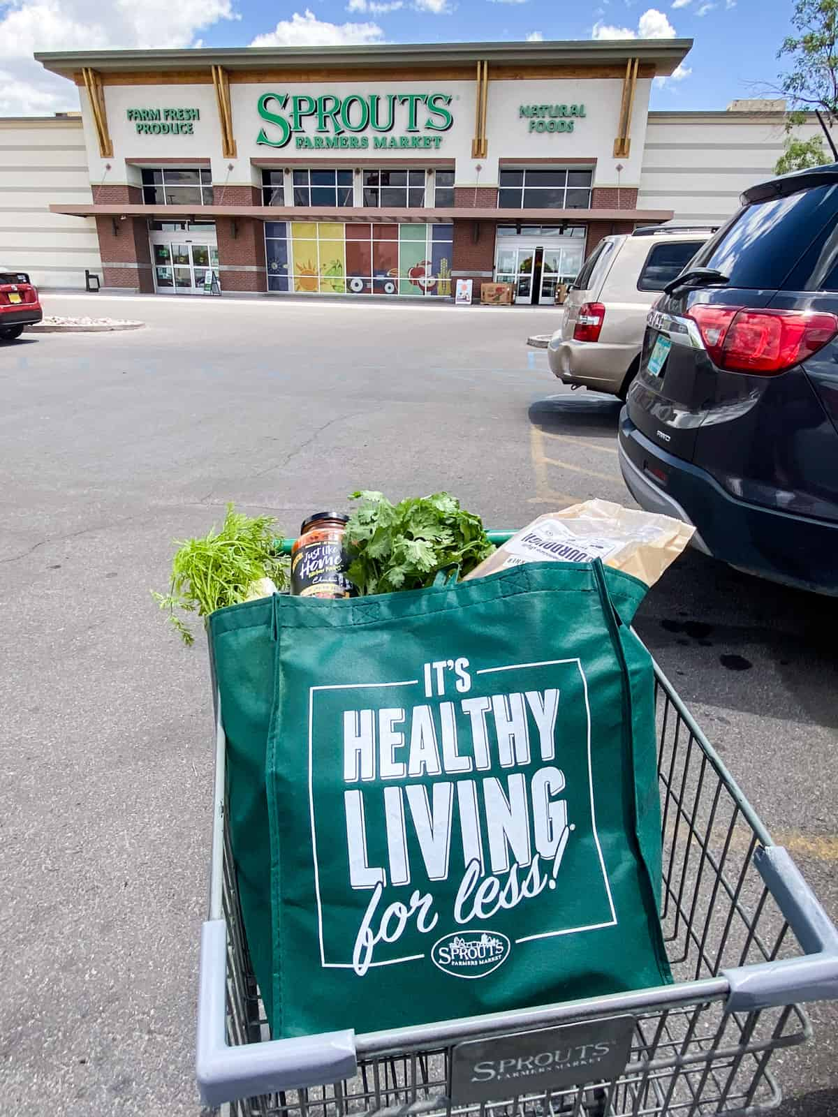 groceries in sporuts bag in cart in front of sprouts