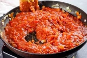 stirrign in the pasta sauce