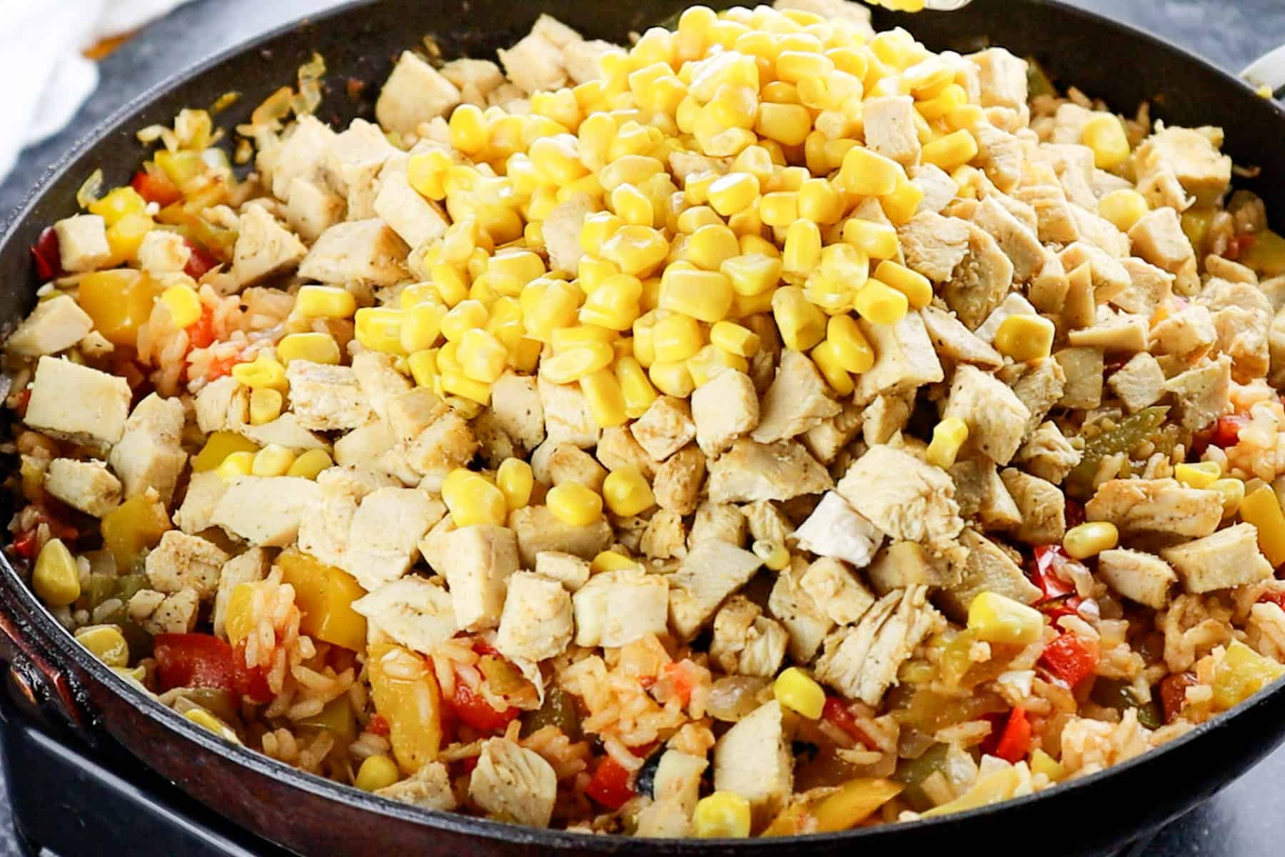 adding corn and chicken to skillet